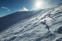 Skiers go down the snowy mountain hill Stock Photo