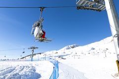 Skiers going up on the chairlift against bright blue sky- ski resort in Italy on sunny winter day.  Stock Photos