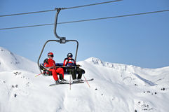 Skiers going up with a ski lift Stock Images