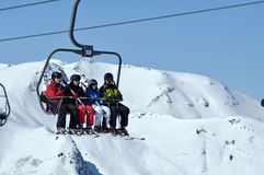 Skiers going up with a ski lift in a ski resort Royalty Free Stock Image