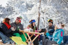 Skiers group refreshing with drink after skiing. In cafe on ski terrain Royalty Free Stock Photos