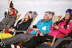 Skiers group sunbathing in sunbed on ski terrain. Skiers group resting and sunbathing in sunbed in cafe on ski terrain Royalty Free Stock Image