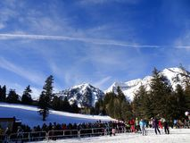 Skiers line up for lift at the mountain. Winter sports at the snow covered mountain royalty free stock photos