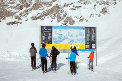 Skiers look at information board in mountain ski resort Royalty Free Stock Images