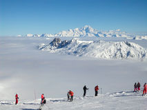 Skiers looking at the Mont Blanc over a sea of clouds Stock Images