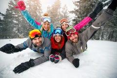 Skiers lying on snow and having fun Stock Photos