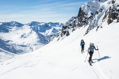 Skiers moving uphill on hot sunny day in the Alaska backcountry. Two skiers skinning uphill on a hot sunny day in the Alaska backcountry of the Talkeetna royalty free stock photos