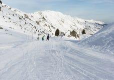 Skiers on a piste in alpine ski resort Royalty Free Stock Image