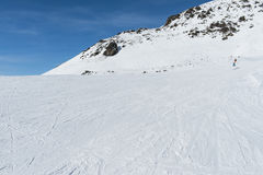 Skiers on a piste in alpine ski resort Royalty Free Stock Images