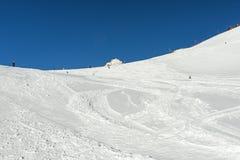 Skiers on a piste in alpine ski resort Stock Photography