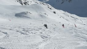 Skiers on piste going downhill stock video