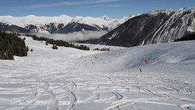 Skiers on piste going downhill stock video footage