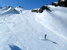 Skiers on piste. High mountain piste ski trails in the Austrian alps with skiers Stock Image