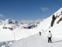 Skiers on piste on sunny day Royalty Free Stock Images