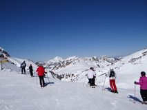 Skiers prepare to descend the piste Royalty Free Stock Images