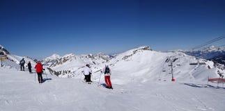 Skiers prepare to descend the piste Stock Photos
