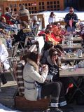 Skiers relax on a sunny deck Royalty Free Stock Photo