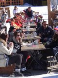 Skiers relax on a sunny deck Stock Photo