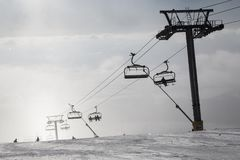 Skiers ride the chairlift in the fog. Stock Image