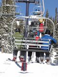 Skiers ride the chairlift through a spruce forest Stock Photo