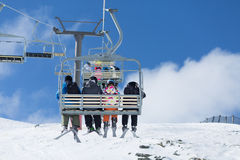 Skiers  ride the ski chair lift. QUEENSTOWN, NEW ZEALAND - AUGUST 6: Unidentified skiers  ride the ski chair lift up the Remarkables Ski Area on August 6 2015 in Royalty Free Stock Image