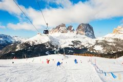 Skiers riding on the ski slope in winter Dolomites, Italy