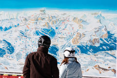 Skiers with safety helmets in front of ski map Royalty Free Stock Images