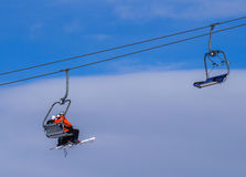 Skiers sitting in ski lift Royalty Free Stock Photos