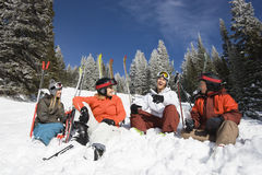 Skiers Sitting in Snow Talking. Group of male and female skiers sitting in the snow relaxing talking and smiling. Horizontal shot Royalty Free Stock Images