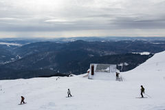 Skiers and skaters on mountains Royalty Free Stock Photography
