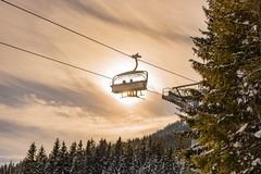 Skiers on the ski chairlift on the the background of the sun and a blue sky. royalty free stock photos