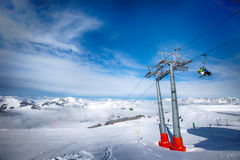 Skiers on ski lift enjoying the view to foggy Alps in Austria and beautiful snowy country panorama in famous Kitzbuehel mountain s Royalty Free Stock Photography