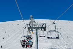 Skiers on a ski lift and piste royalty free stock photography
