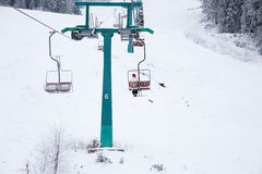 Skiers on ski-lift in snow mountains at winter day. cable car li Stock Photography