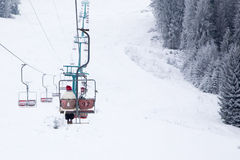 Skiers on ski-lift in snow mountains at winter day. cable car li Stock Photo