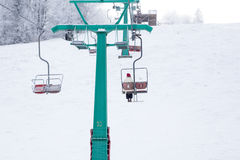 Skiers on ski-lift in snow mountains at winter day. cable car li Royalty Free Stock Image