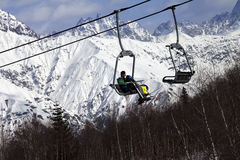Skiers on ski-lift and snow mountains at winter sun day Stock Photos