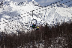 Skiers on ski-lift in snow mountains at winter sun day Stock Image