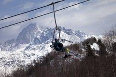 Skiers on ski-lift in snow mountains at winter sun day Stock Photos