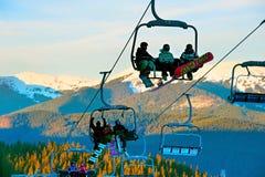 Skiers on ski lift at sunset Stock Photo