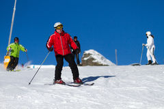 Skiers on ski slope. Male skier heading down ski slope with three other skiers in the background Stock Image
