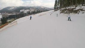 Skiers skiing down on slopes in Bukovel ski resort. stock footage
