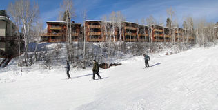 Skiers slide past expensive townhouses Stock Photography