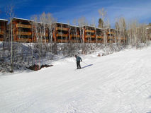 Skiers slide past expensive townhouses Royalty Free Stock Photos