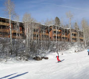 Skiers slide past expensive townhouses Stock Image