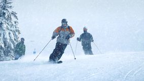 Skiers On Slope With Snow Falling