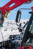 Skiers and snow-grooming machine Royalty Free Stock Photography