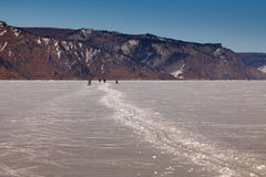 Skiers on the snow path. People are running on the ice of Baikal lake Stock Images