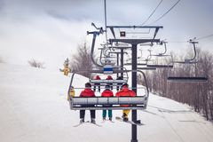 Skiers and snowboarder on a chairlift royalty free stock image