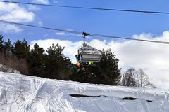 Skiers and snowboarders on chair-lift in winter mountain Stock Images